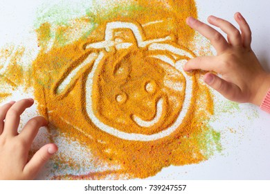 A child paints a funny face with colored sand on a white sheet