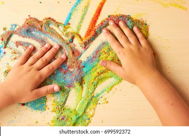 The child paints on the table with colored sand.
