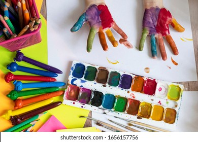 The child paints. Palms and hands of a child in multi-colored watercolor. Watercolor, gouache, paint brushes, colored and wax crayons, stickers. Set for drawing, creativity and hobbies