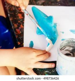 A child paints a shark