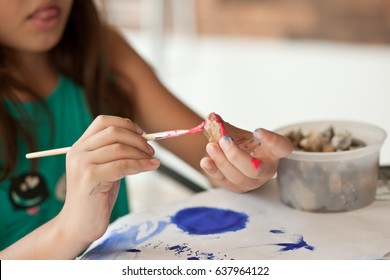 The child paints stones