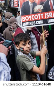 A child with the Palestinian flag pained on his cheek holds a sign calling for people to boycott Israel. Al Quds Day rally, London, 10/06/18.