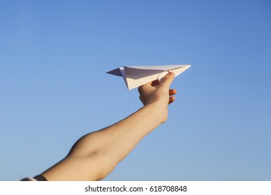 Child with paper air plane against blue sky