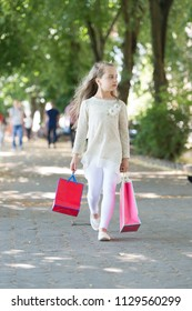 Child with paper bags in summer. Girl with shopping bags walk in park. Kid shopper in fashion clothes outdoor. Shopping on sale and purchase. Little princess with crown on long blond hair.