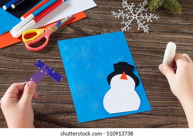 Child paper glued details. The child makes a greeting card with a snowman. Glue, paper, scissors on a wooden table. Children's art project, a craft for children.