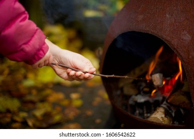 Child and parent toasting a marshmallow on an outdoor fire