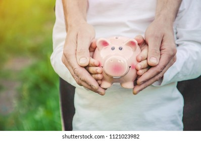 The child and parents are holding a piggy bank in their hands. Selective focus.
