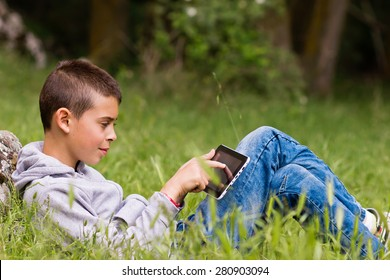 Child in the park with tablet in hands