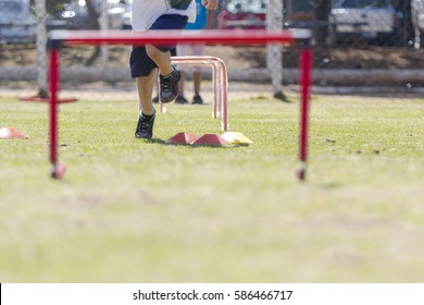 Child participating in an athletics class, running on a lawn and jumping a barrier with discs on his way