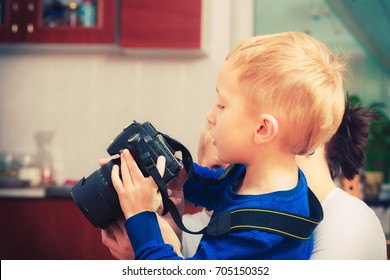 Child passion and hobbies concept. Kid playing with big professional digital camera, photographing various things in house