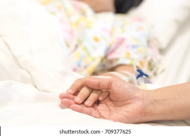Child patient with IV line in hand sleep on hospital bed with mother's hand holding together to support ill daughter.Medical palliation healthcare concept