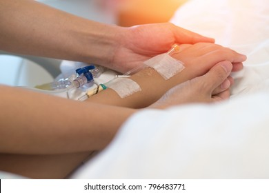 Child patient with IV line in hand sleep on hospital bed with hands of mother or doctor holding together to support ill daughter.Medical palliation healthcare concept