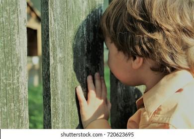 Child peaking through fence playfully.