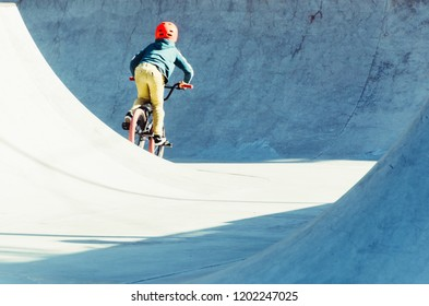 child pedaling in his bicycle in a bmx park