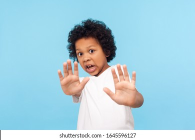 Child phobia. Portrait of scared little boy looking terrified panicked at camera and showing stop gesture as if trying to defend himself, screaming in fear. studio shot isolated on blue background