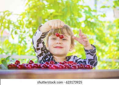 The child is picking cherries in the garden. Selective focus.