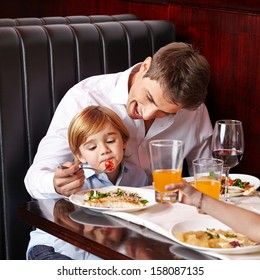 Child is a picky eater in restaurant and father tries to feed it