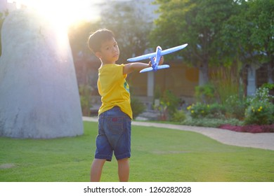 Child pilot aviator with airplane dreams of traveling in summer in yellow shirt and blue airplane at sunset