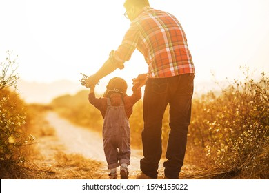 Child pilot aviator with airplane dreams of traveling in summer in nature at sunset,Happy kid playing with father. Dad and son outdoors.   Travel and vacation concept. Imagination and freedom concept