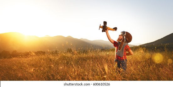 Child pilot aviator with airplane dreams of traveling in summer in nature at sunset