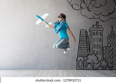 Child pilot jumping. Kid having fun at home. Success, creative and idea concept