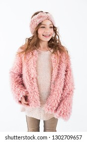 A child in a pink coat posing in the studio, smiling cheerfully broad smile