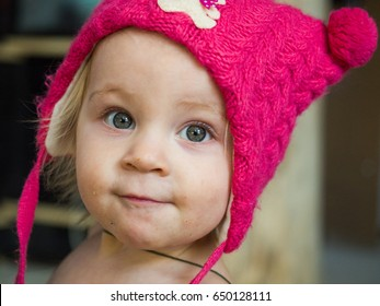 A child in a pink hat.Young girl in the house. Family photo. Professional photo session. Interesting atmosphere and interior. Eco-style. A large portrait.  Natural female nature.