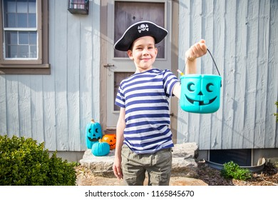 child in a pirate costume holding a teal bucket. trick-or-treating. Teal Pumpkin. Alternative non-food treats for kids with food allergies. the concept of health for children in the Halloween season