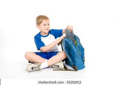 A child places a folder in his backpack