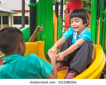 Child play on playground concept. Asian boy brother and girl child sister play standing on slider in playground park in school on morning. Brother safe to holding hand sister.