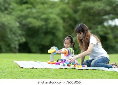 child play toy with mom in park happily.