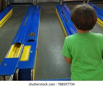 child playing an arcade game rolling a ball on a ramp
