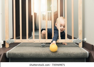 child playing behind safety gates in front of stairs at home