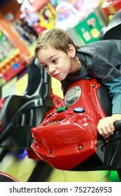 Child playing in bike simulator at indoor playground