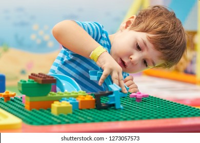child playing and building with colorful plastic bricks table. Early learning and development.