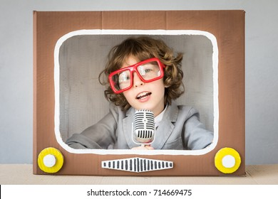 Child playing with cardboard box TV. Kid having fun at home. Video blogging concept