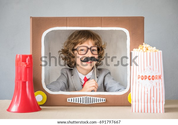 Child playing with cardboard box TV. Kid having fun at home. Communication concept