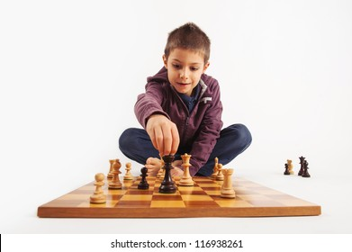 Child playing chess, isolated on white background.