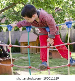 Child playing at children playground, climbing on  rope ladder obstacle course equipment.