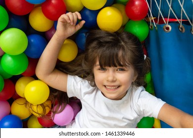 Child playing with colorful balls in playground ball pool. Activity toys for little kid. Kids happiness emotion having fun in ball pit on birthday party in kids amusement park or indoor play center.
