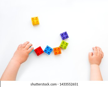 Child is playing with colorful constructor blocks. Kid's hands with bricks toy on white background. Educational toy, flat lay, top view.