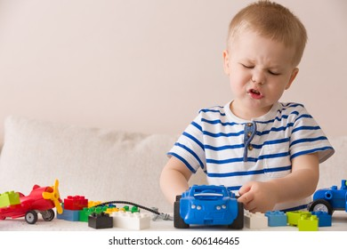 Child playing with colorful plastic bricks at the table. Toddler having fun and building out of bright constructor bricks. Early learning.  stripe background. Developing toys