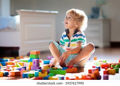 Child playing with colorful toy blocks. Kids play. Little boy building tower of block toys sitting on dark floor in sunny white bedroom. Educational game for baby and toddler. Children build toy house - Shutterstock ID 1937617990