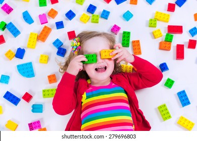 Child playing with colorful toys. Little girl with educational toy blocks. Children play at day care or preschool. Mess in kids room. View from above.