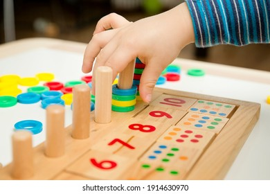 Child playing with different color wooden rings. Sequence, fine motor skills, therapy task for education and brain exercise. Counting math play game.  Montessori type implement. Wooden toys.
