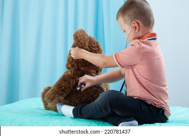 Child playing at doctor with his teddy bear