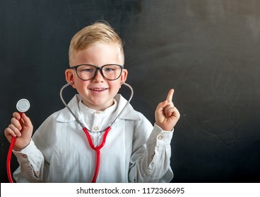 Child playing doctor with stethoscope in hands. Happy smiling kid boy playing at home or daycare.  Education for preschool and kindergarten. Pediatric, healthcare and people concept.