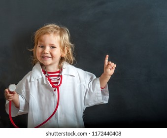 Child playing doctor with stethoscope in hands. Happy smiling kid girl playing at home or daycare.  Education for preschool and kindergarten. Pediatric, healthcare and people concept.