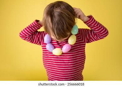 Child playing with an easter egg necklace, easter egg hunt concept.