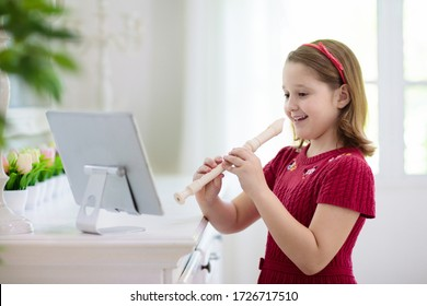 Child playing flute. Remote learning from home. Arts for kid. Little girl with musical instrument. Video chat conference lesson. Online music tuition. Creative children play song. Classical education